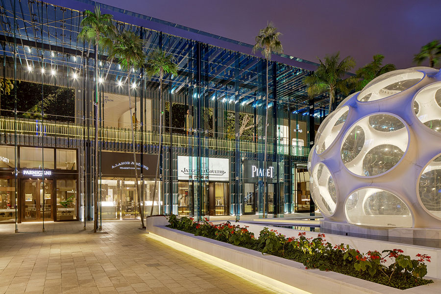 Outside the Miami Design District at night, the store fronts are lit up and an outdoor common area is decorated with a fountain and flowers.