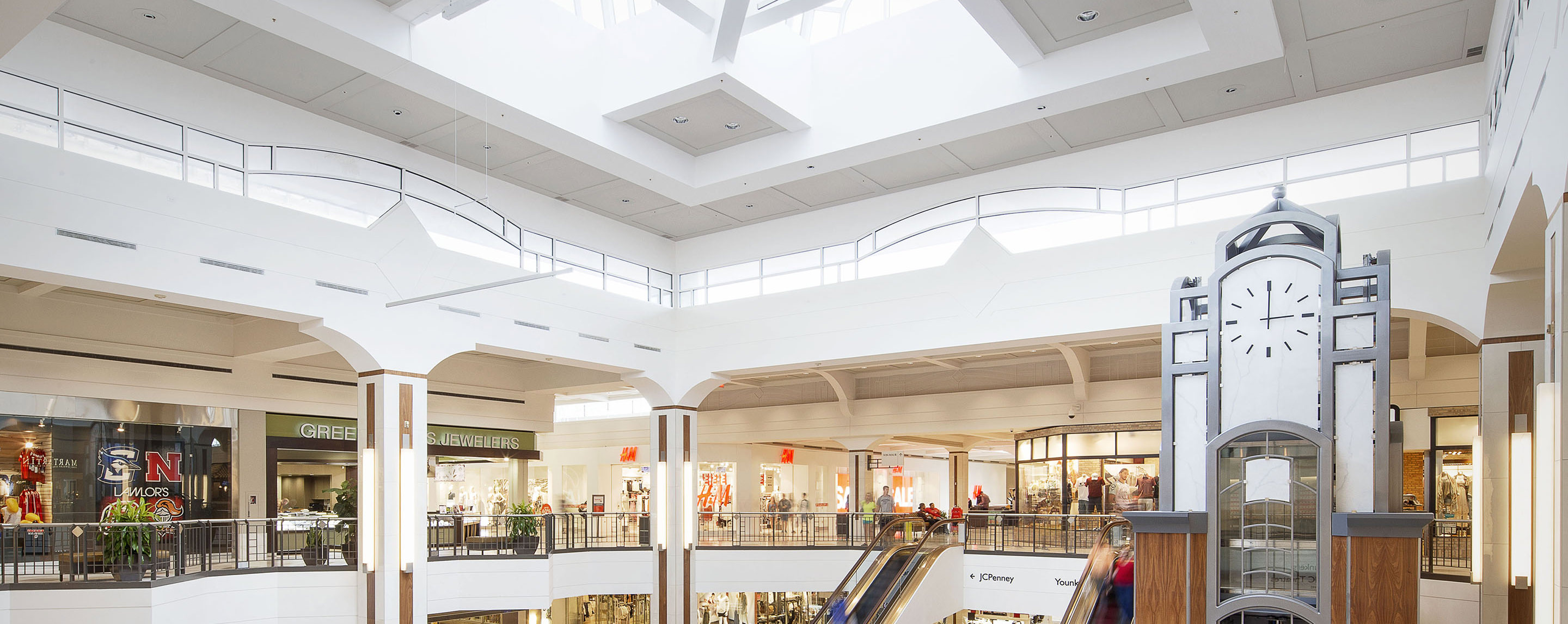 A view from the upper level of Westroads Mall shows several storefronts, escalators, and a clock above the elevator to help guests keep time.