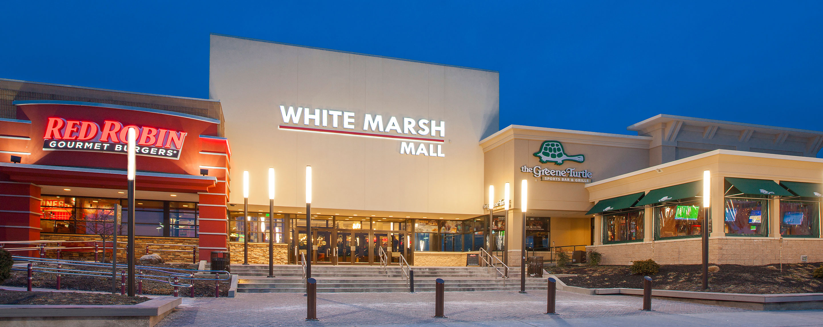 At night, the White Marsh Mall entrance and surrounding landscape is brightly lit by decorative lamp posts.