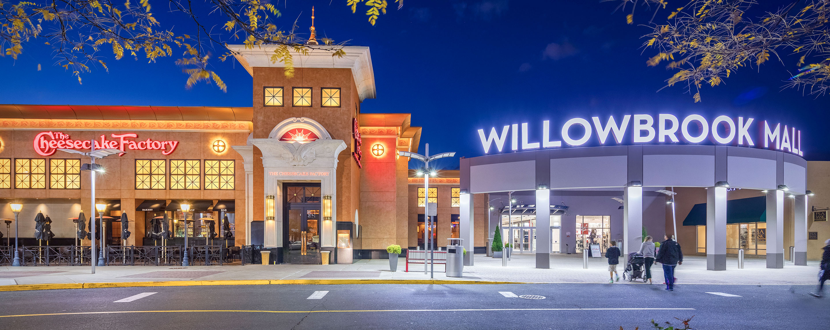 At dusk, the Willowbrook entrance sign and surrounding lights brightly illuminate the outside area.