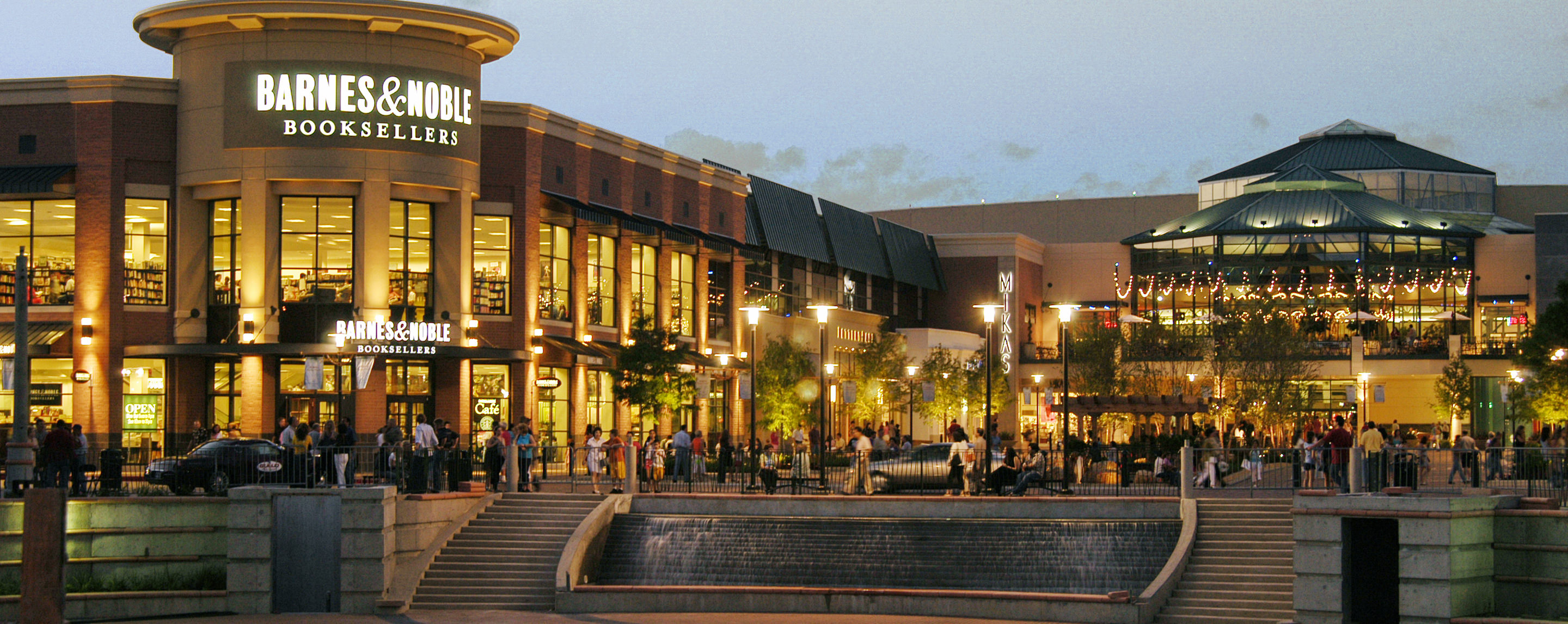 An outside common area at night is light up with a running fountain and areas for shoppers to relax.
