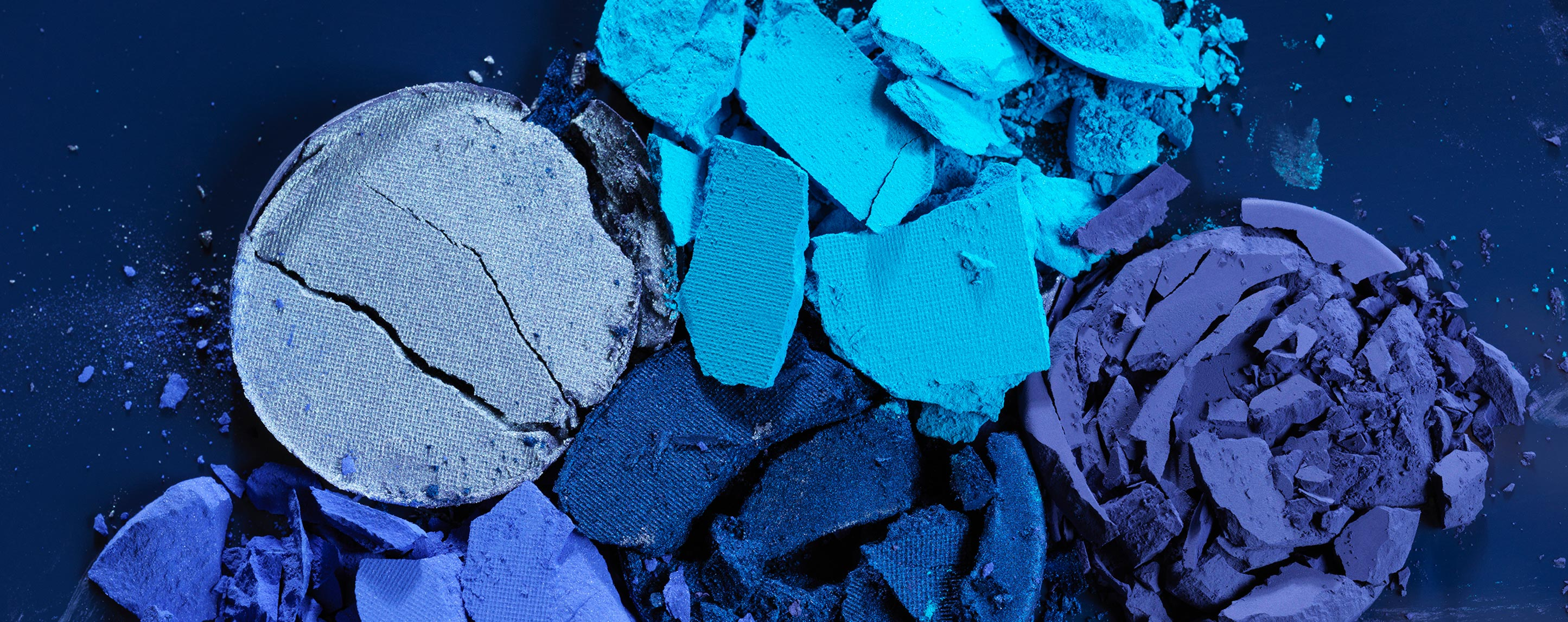 Three stacks of broken makeup powder in various shades of blue and purple sit on an indigo background.