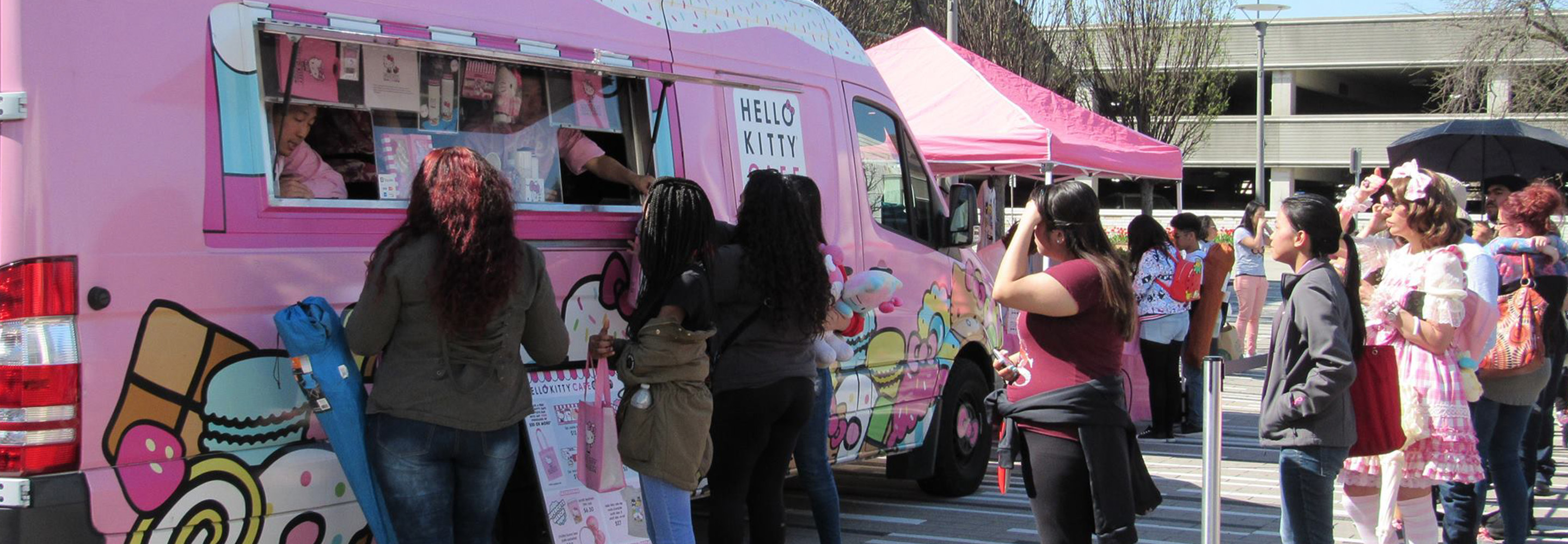 Pink Hello Kitty pop-up truck with consumers around it.