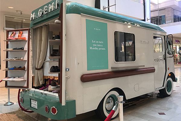 Vintage cream and teal truck selling Italian shoes.